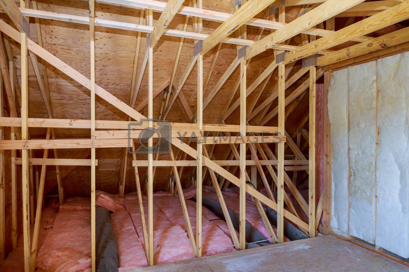 Fiberglass cold barrier insulation material in the sloping attic of a new frame house
