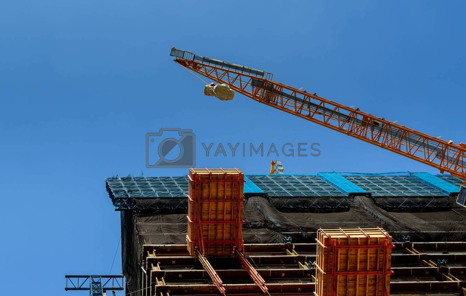 High rise building construction with tower crane against clear blue sky background