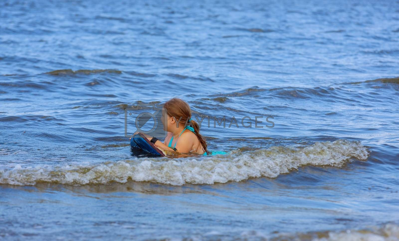 Young girl swimming in the ocean in waves on the beach.