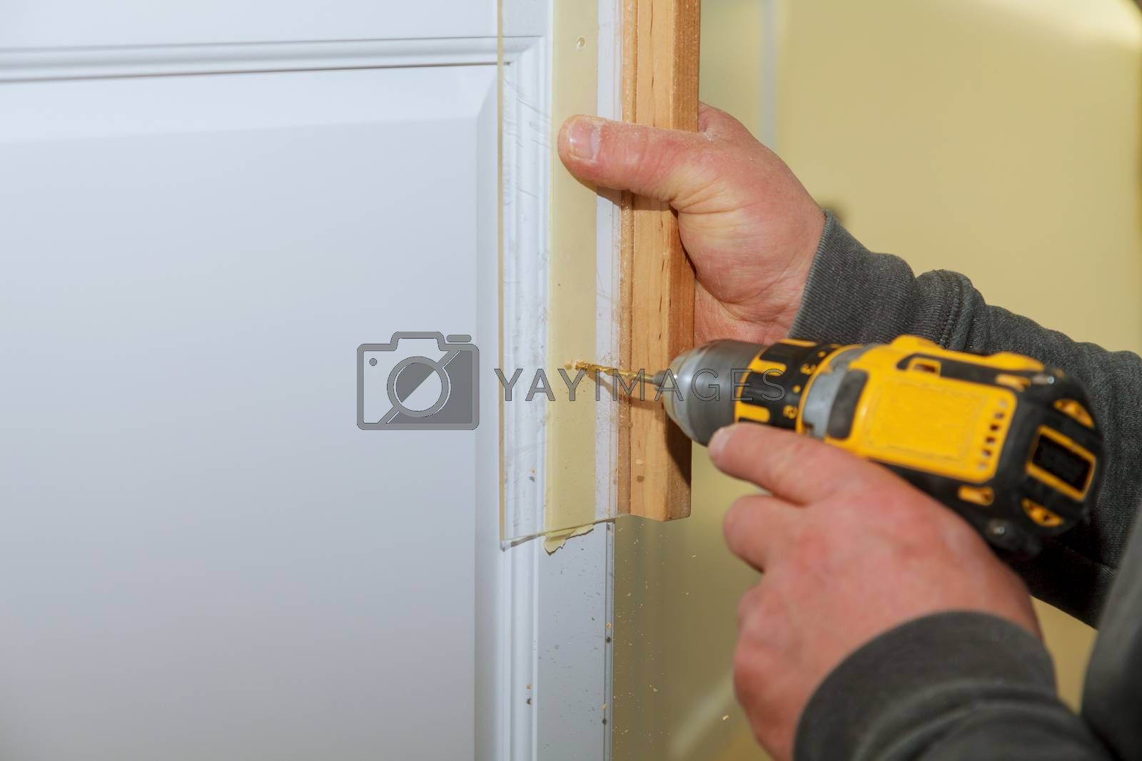 Carpenter working on new kitchen drilling in cabinet a new handle