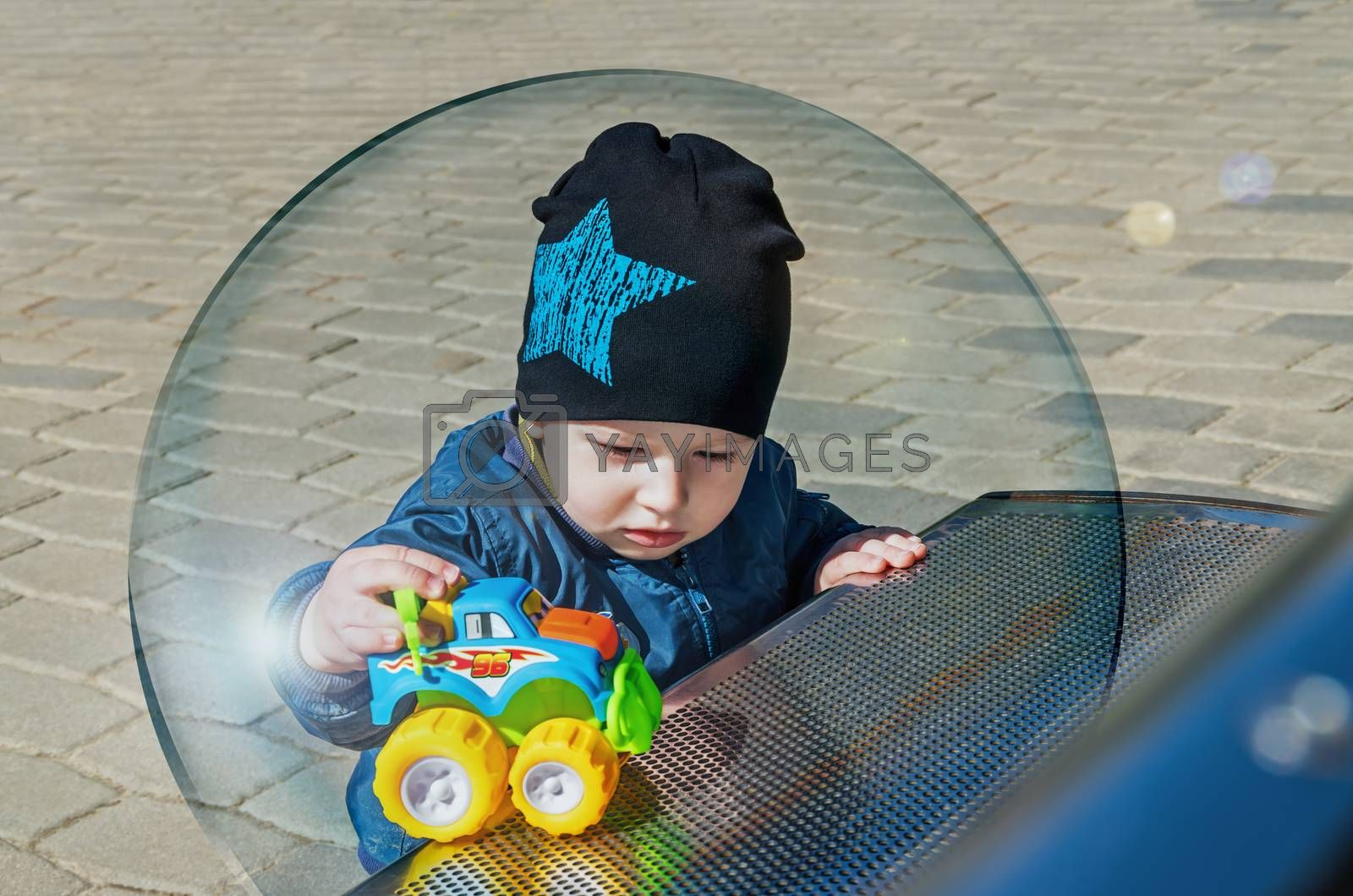 A little boy inside a glass ball symbolizing the protection of children from viral infection