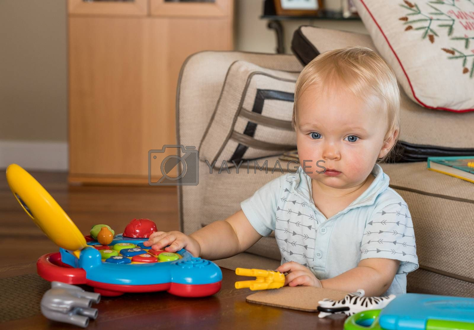 Baby boy sitting on the floor of living room and playing with toy computer and animals