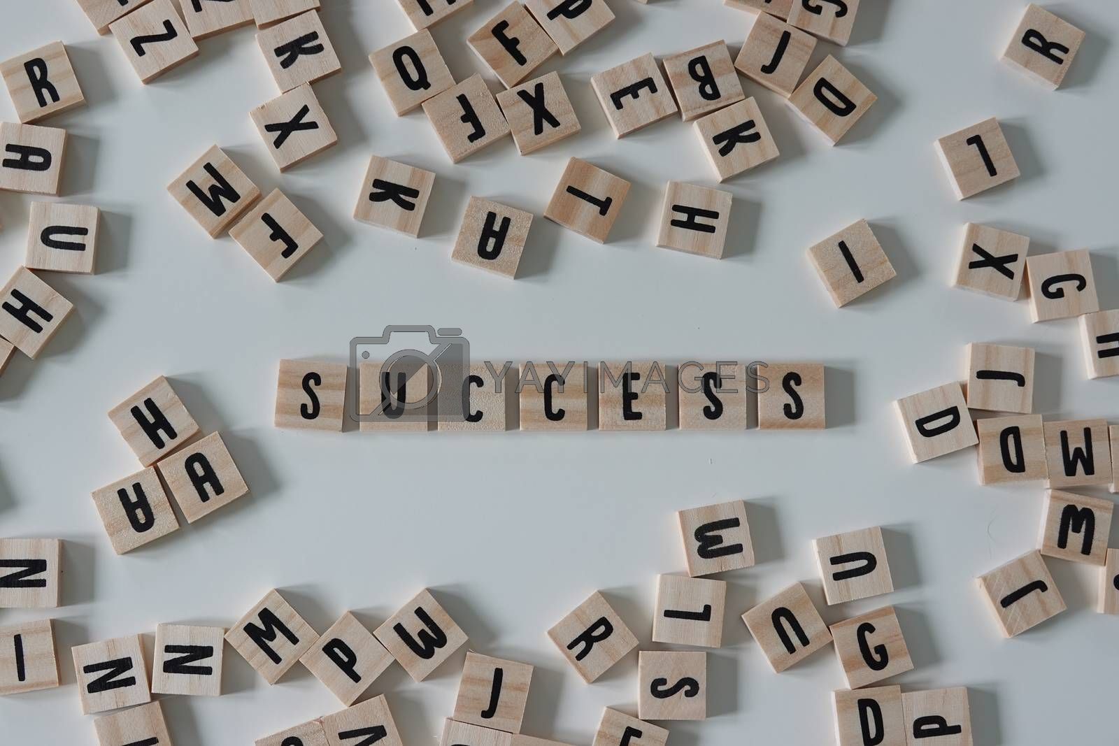 Success written in wooden letter tiles surrounded by random letters on a white background