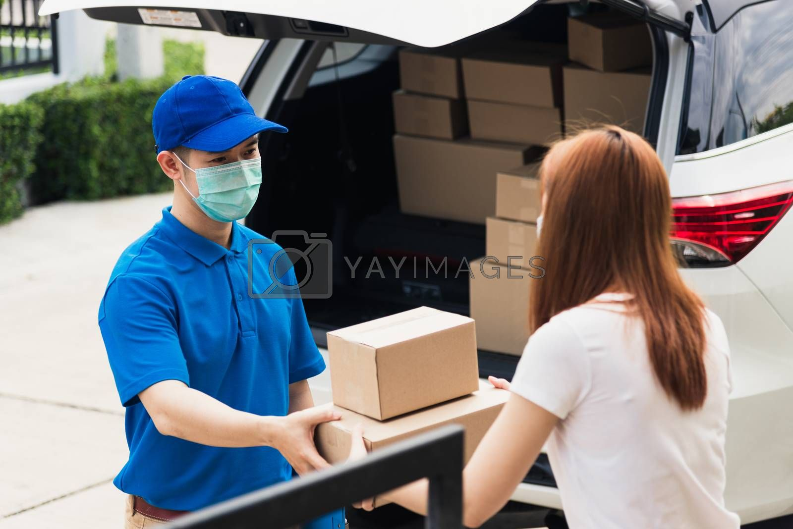 Asian young delivery man courier shopping online give parcel post box he protective face mask and service woman customer receiving boxed at front home door, under curfew pandemic coronavirus COVID-19