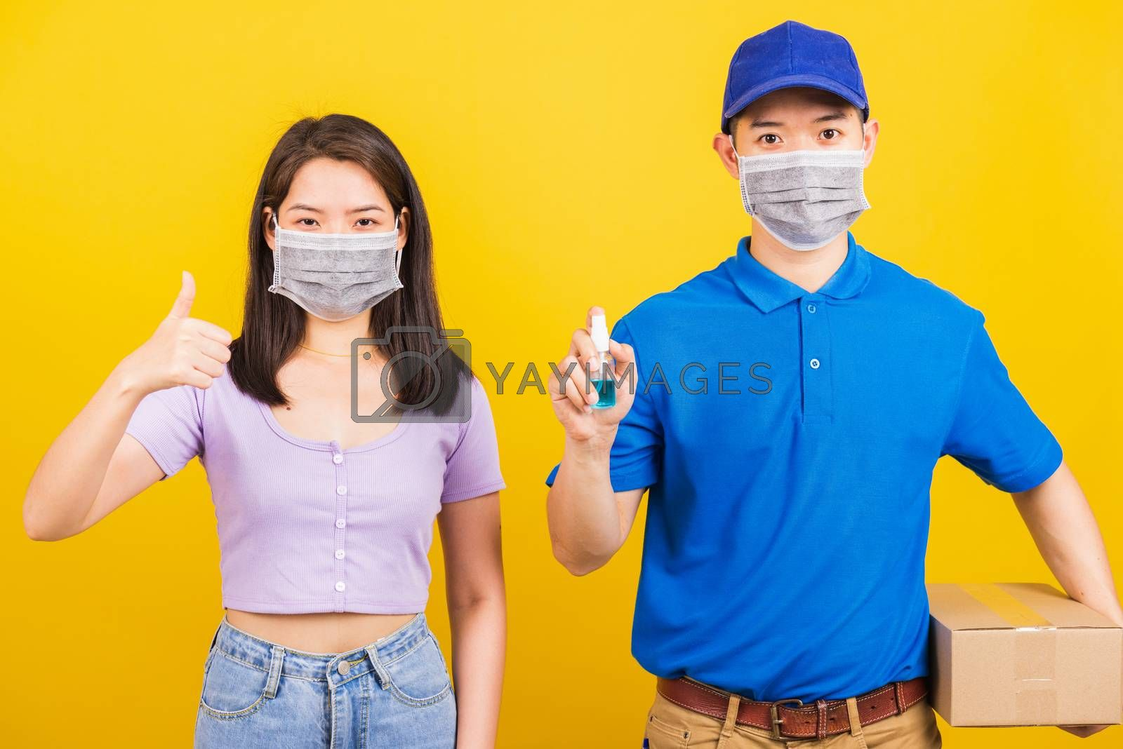 Asian young handsome delivery man hold alcohol disinfectant spray and woman show finger thumb up and both wearing face mask protective  virus, isolated yellow background, outbreak coronavirus COVID-19