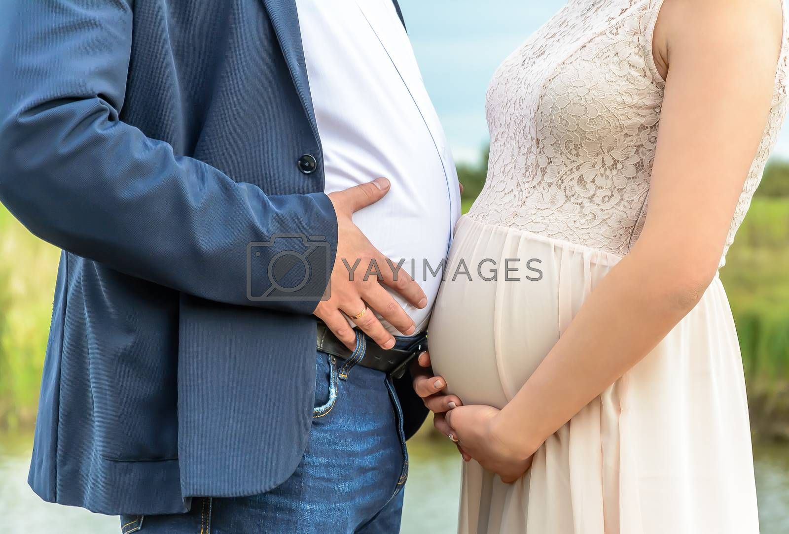 Photo of a pregnant woman and a potbellied man