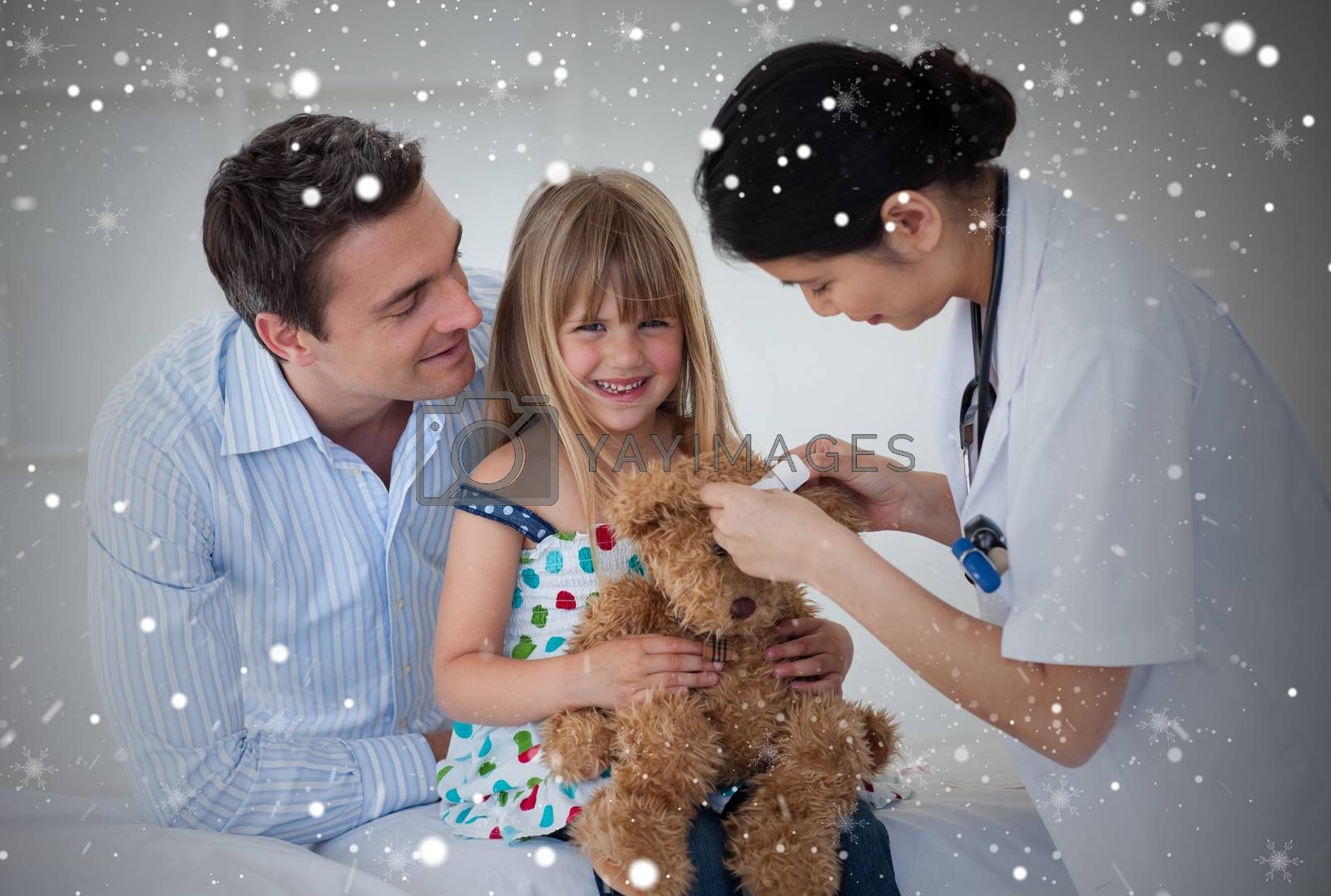 Smiling patient examining a teddy bear with a doctor against snow