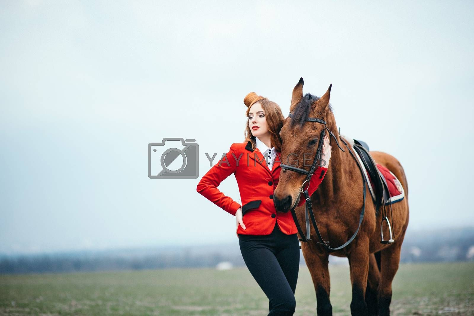 red-haired jockey girl in a red cardigan and black high boots with a horse for a walk