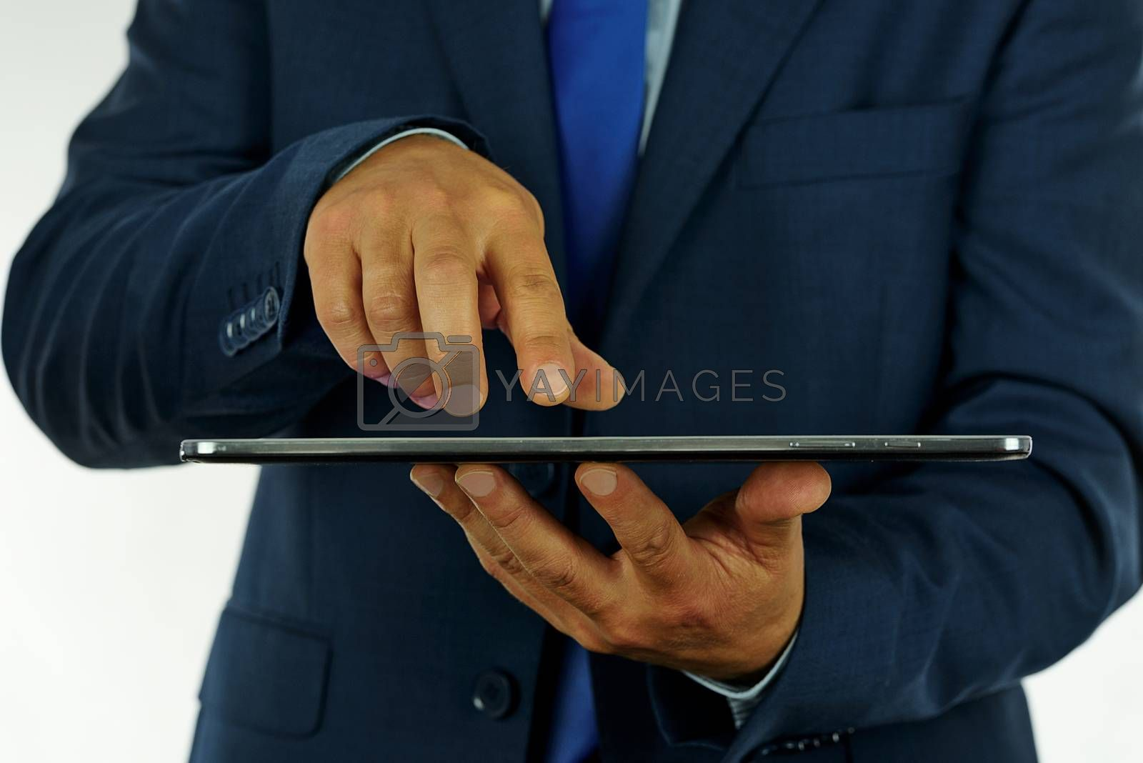 Photo of an elegant businessman working on a digital tablet in the office.