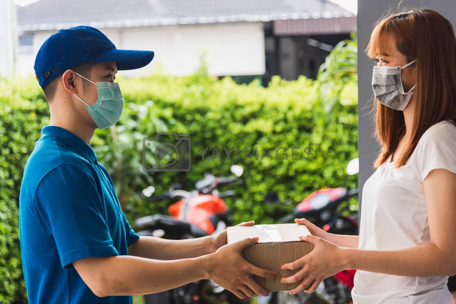 Asian young delivery man courier with package post box in uniform he protective face mask he making service woman customer receiving front house under curfew quarantine pandemic coronavirus COVID-19