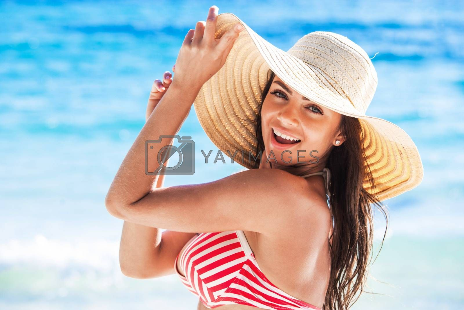 Beach woman relaxing on travel vacation smiling happy and cheerful in summer sun. Beautiful ?aucasian woman wearing white beach hat and bikini on tropical paradise beach.