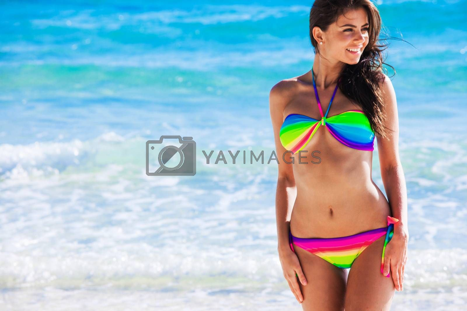 Portrait of pretty beautiful fashion woman in bikini posing in summer near the sea with gorgeous smile in happy mood on tropic island on vacation