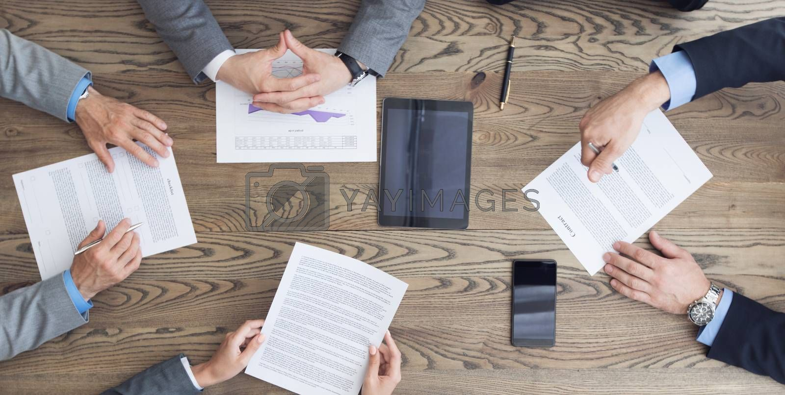 Top view of confident business men in suits sitting at wooden table and discussing new contract terms before signing it top view