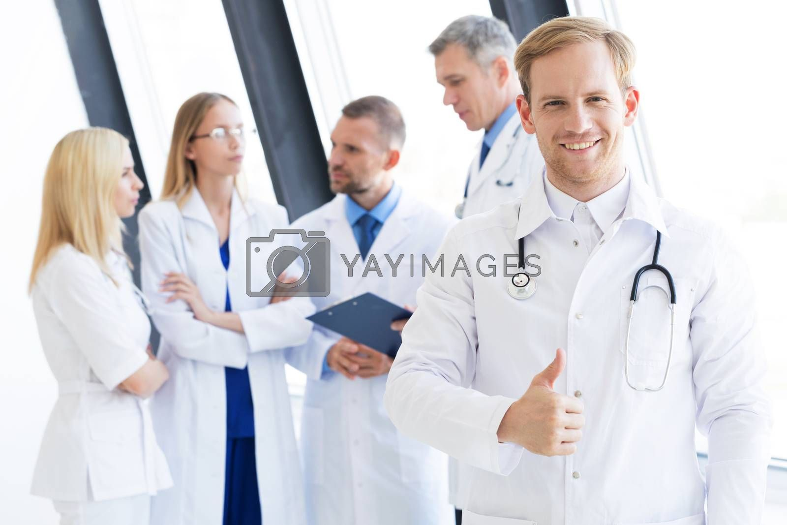 Team of medical professionals, young doctor looking at camera, smiling, showing thumb up