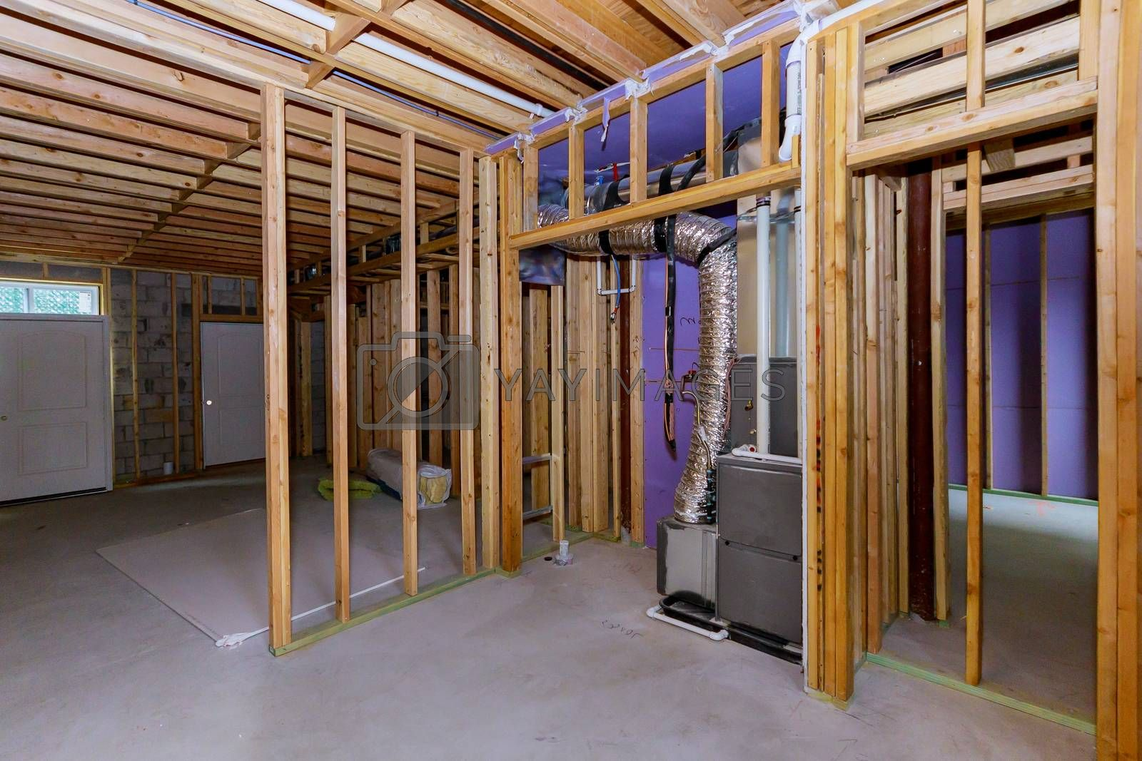 Interior view of a basement under construction home framing with beam in home heating system