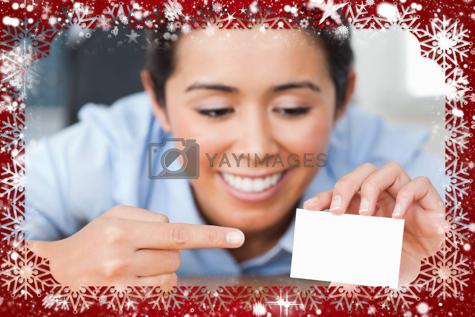Composite image of beautiful woman showing her visiting card against snow