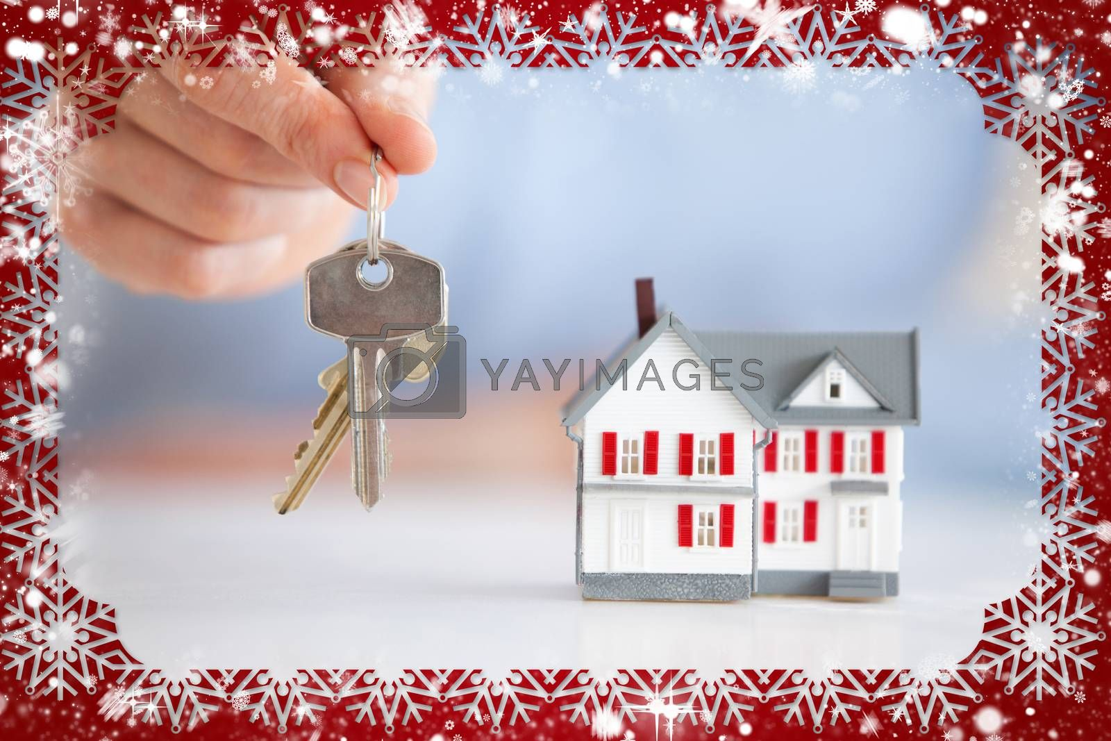 Woman holding keys next to a model house against snow