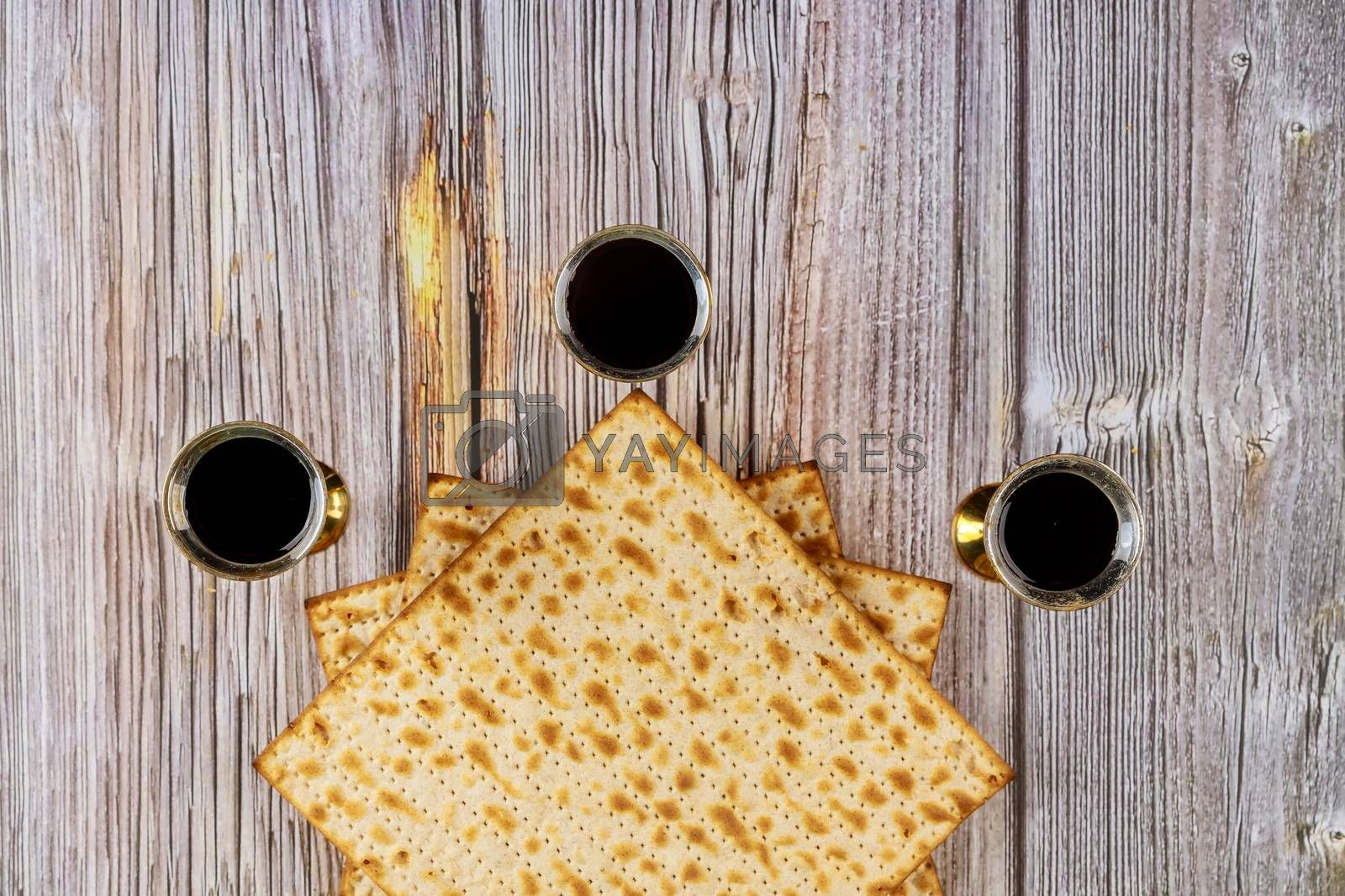 Passover matzoh jewish holiday bread and kosher wine over wooden table