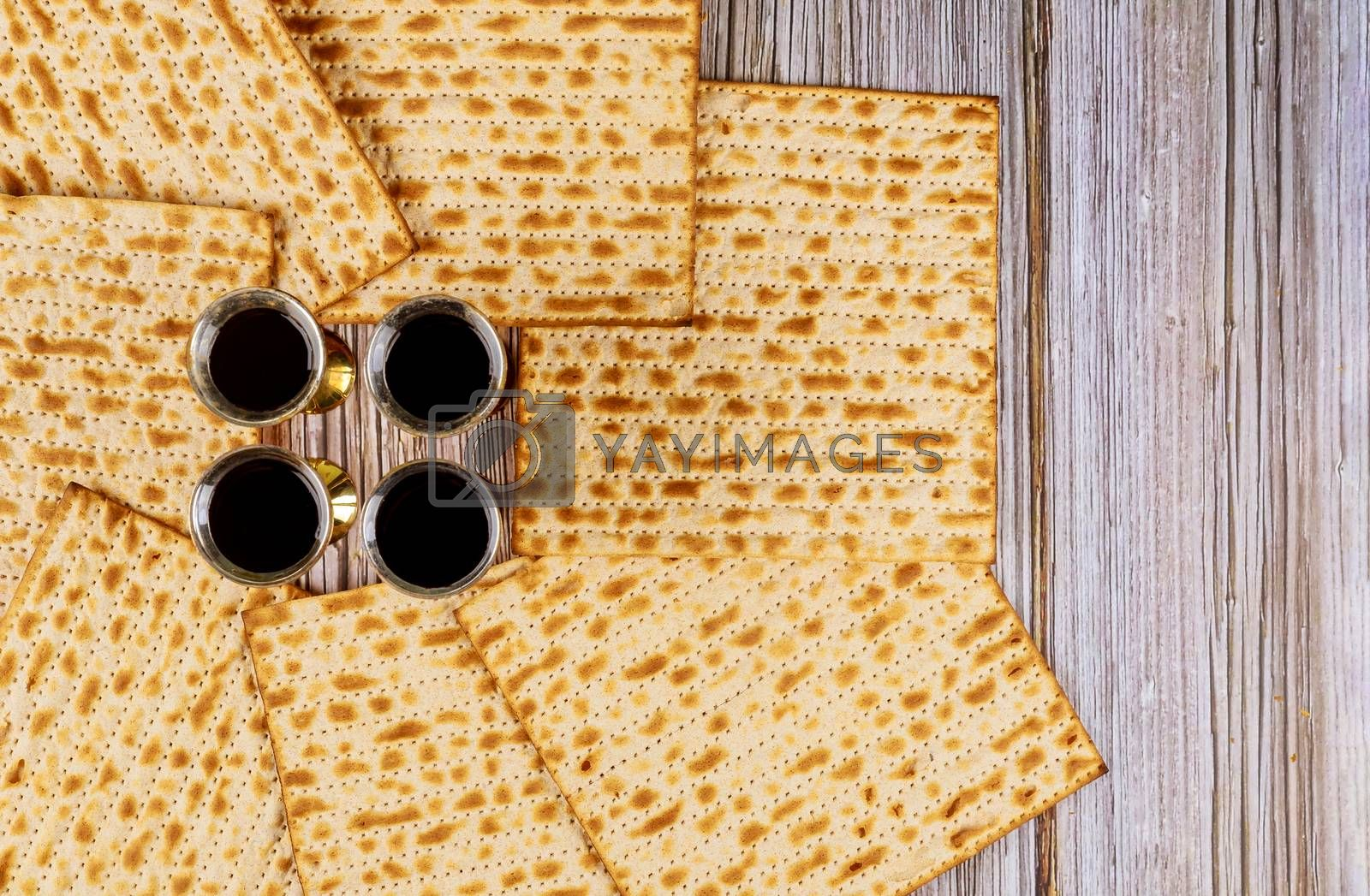 Passover matzoh jewish holiday bread and four glasses kosher wine over wooden table background.