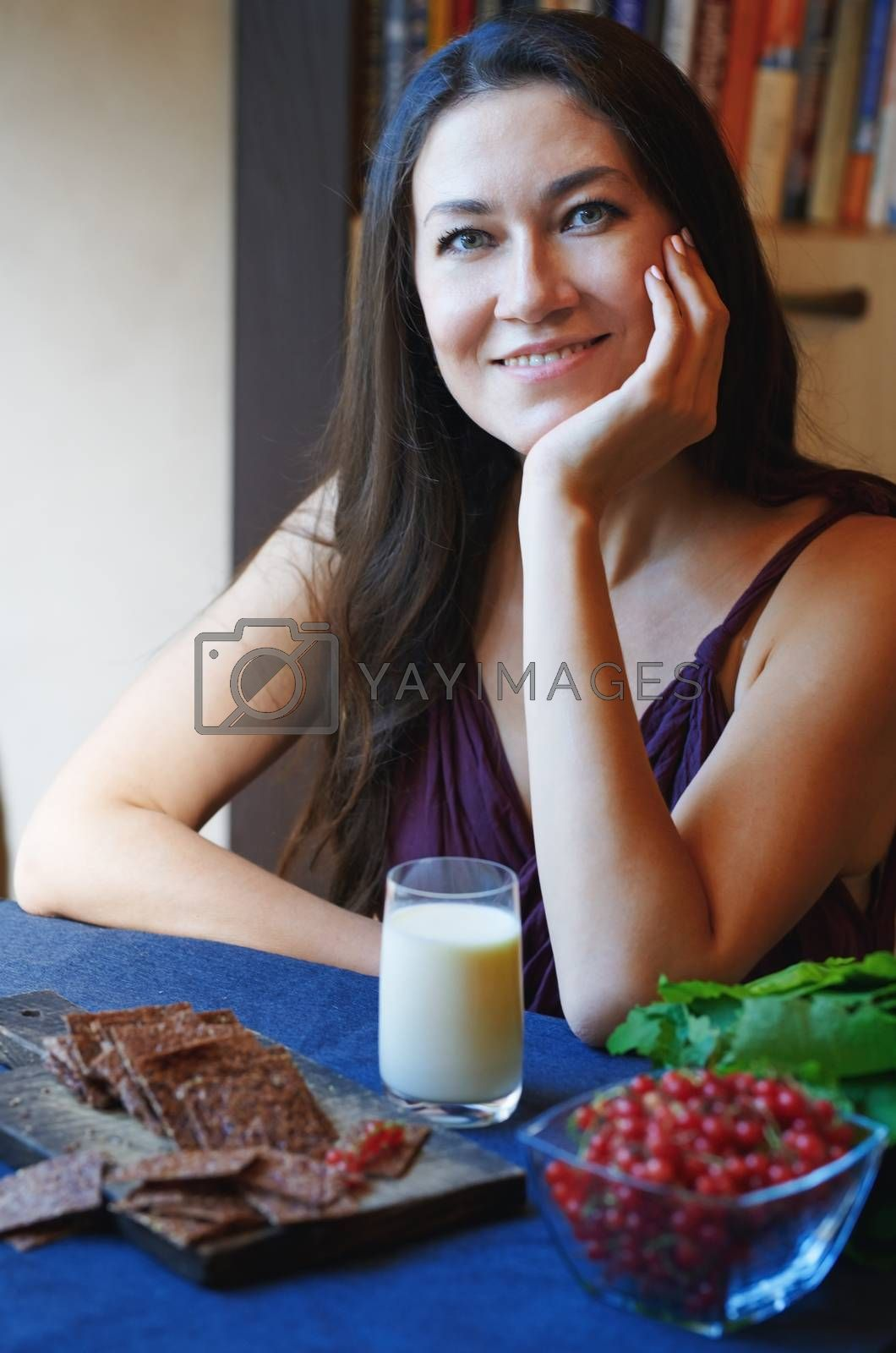 Vegan woman sitting at the table with healthy food