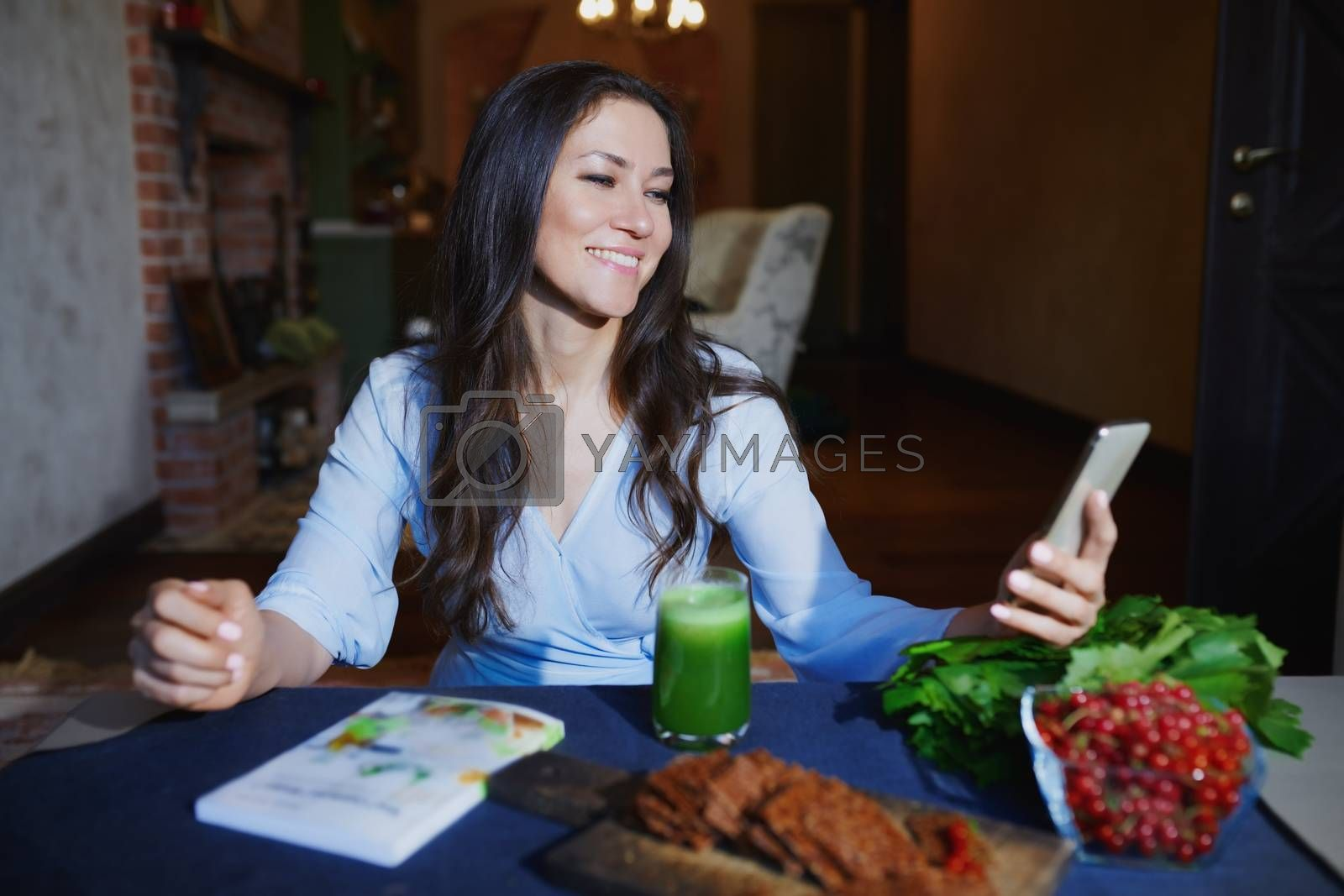 Royalty free image of Woman at the table with healthy food making mobile photo selfie  by Novic