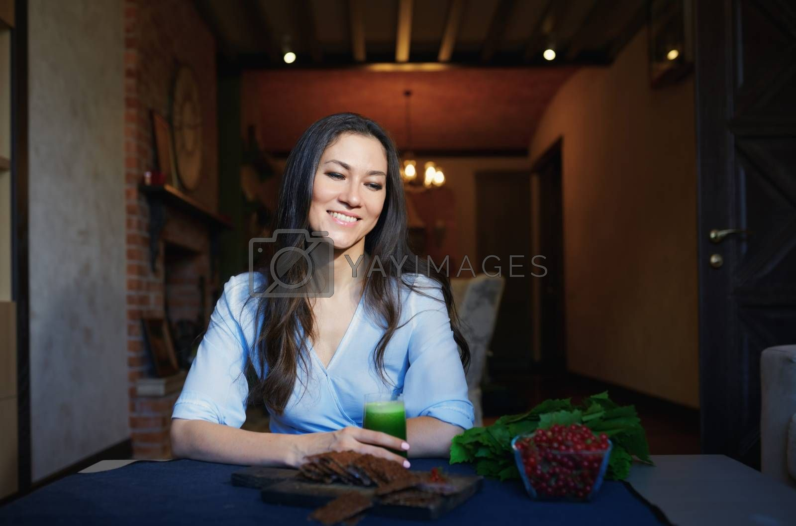 Smiling vegetarian woman sitting at the table with celery fresh  by Novic