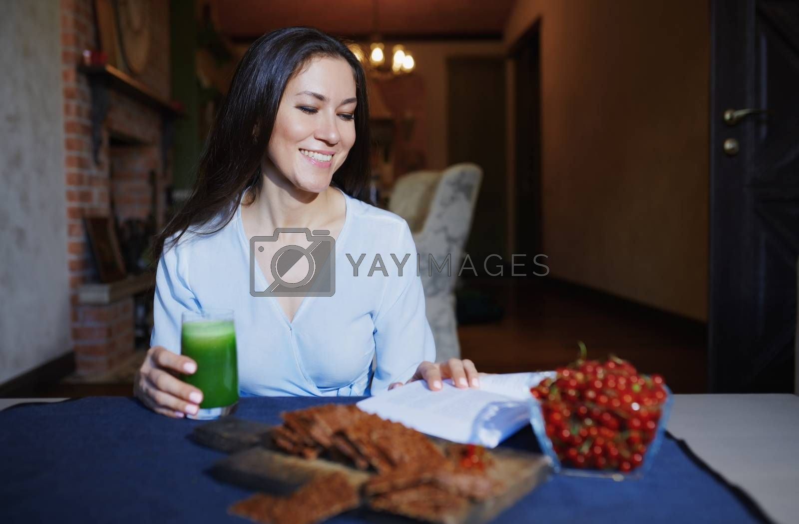 Smiling vegetarian woman sitting at the table with celery fresh juice, flaxseed bread and berries and reading book
