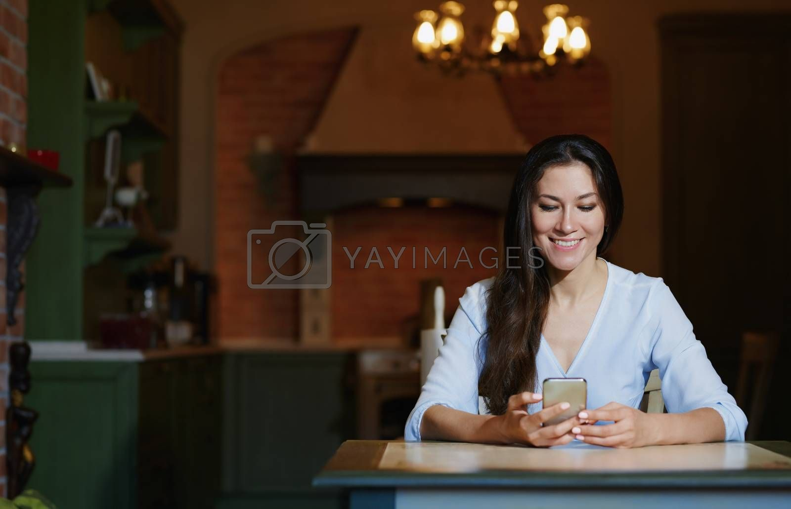 Smiling woman sitting and table and using smartphone by Novic