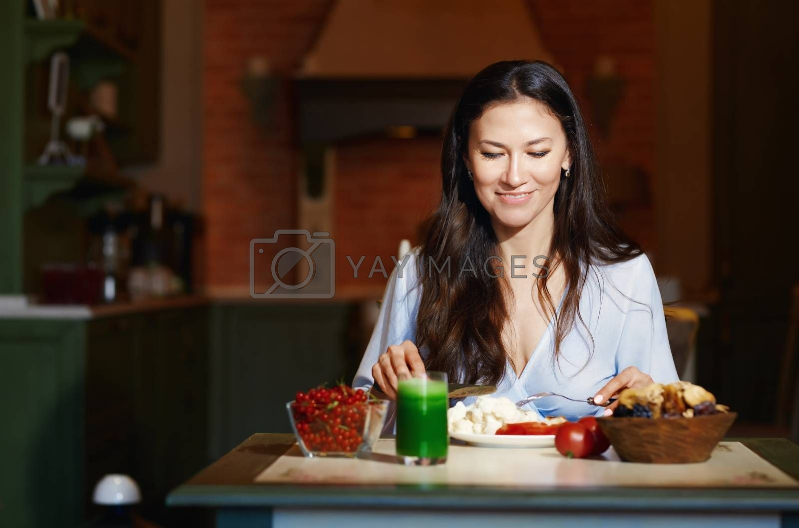Smiling vegetarian woman sitting at the table and eating healthy food