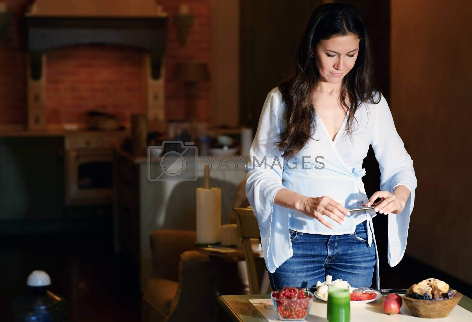 Woman making mobile photo of healthy food for her Internet blog