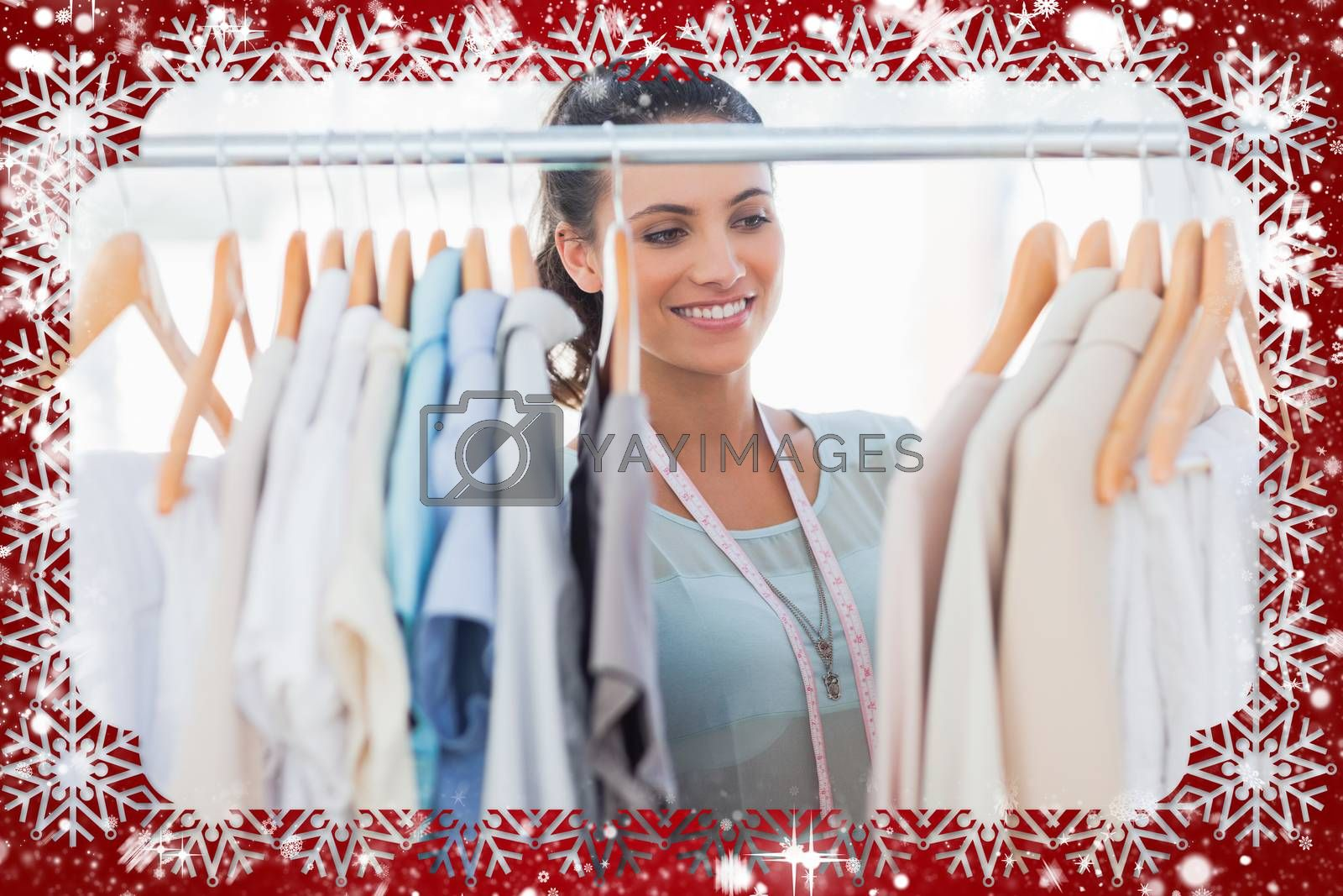 Attractive fashion designer looking at clothes against snow