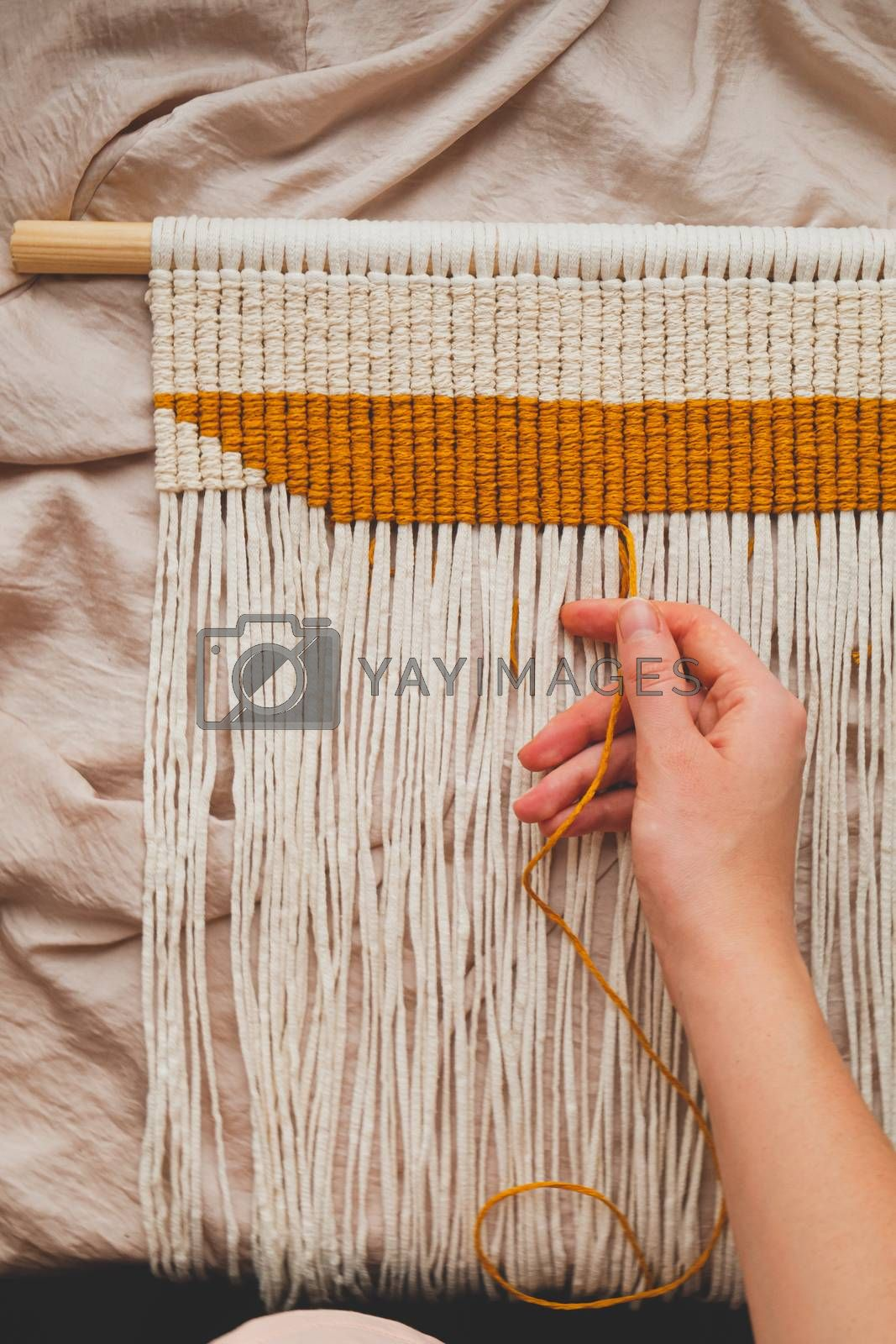Handcrafted macrame wall hanging, close-up view. Human hand making a piece of decor