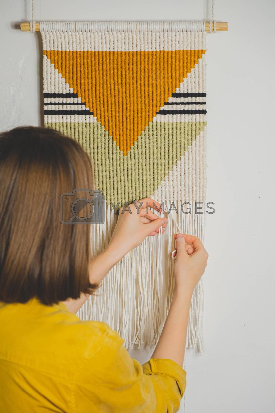 Woman doing macrame craft. Hand-making a cotton rope wall-hanging decor piece, concept of handicraft hobby or handworking