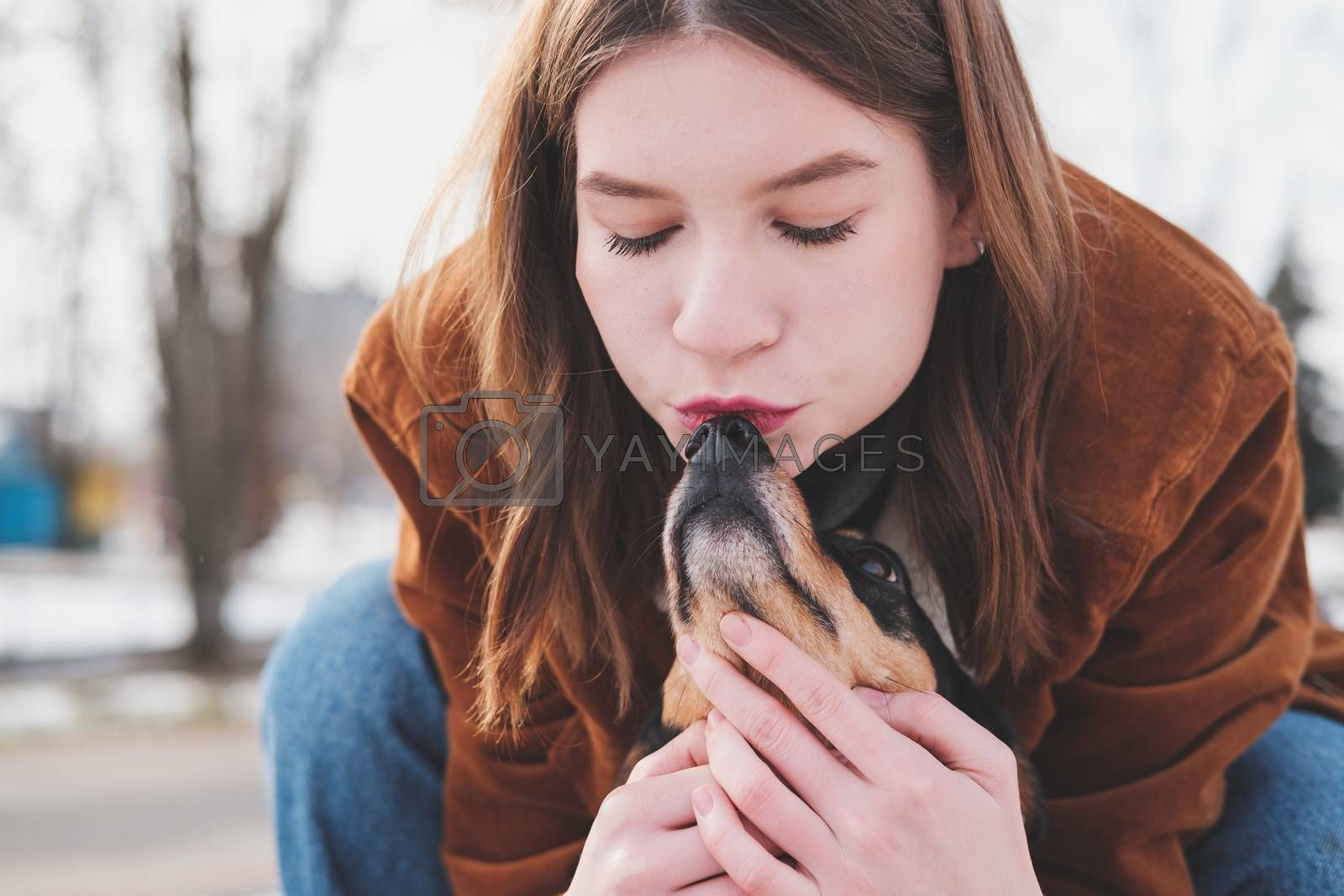 Loving and adoring pets concept: Young woman kisses her little dog