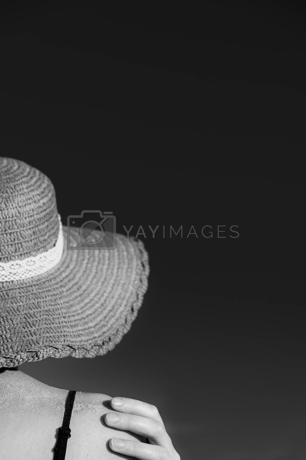 Summer holidays mood: female in beach hat, covered in sand in monochrome low key. Shoulders of a young woman in a retro hat, shot from behind