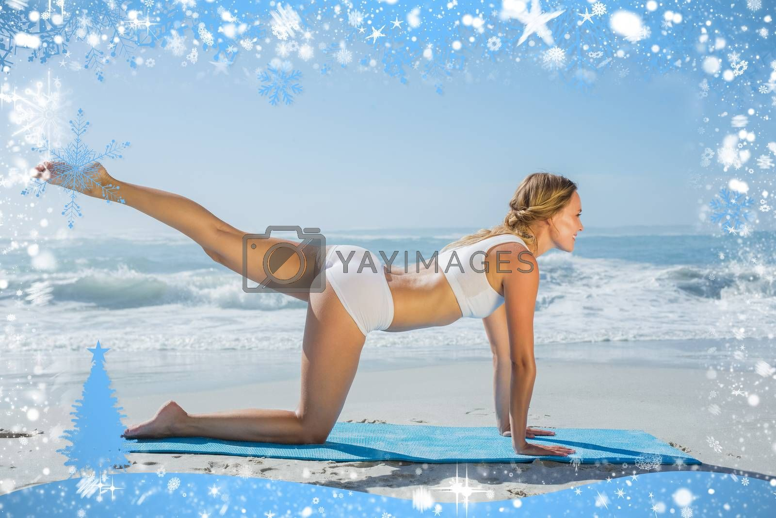 Gorgeous fit blonde in pilates pose on the beach against snow