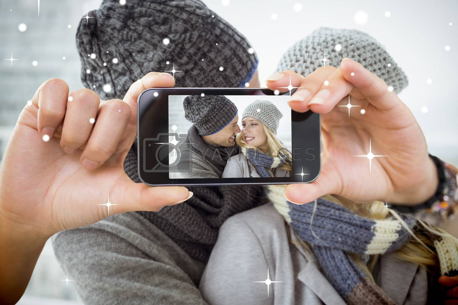 Hand holding smartphone showing photo against snow