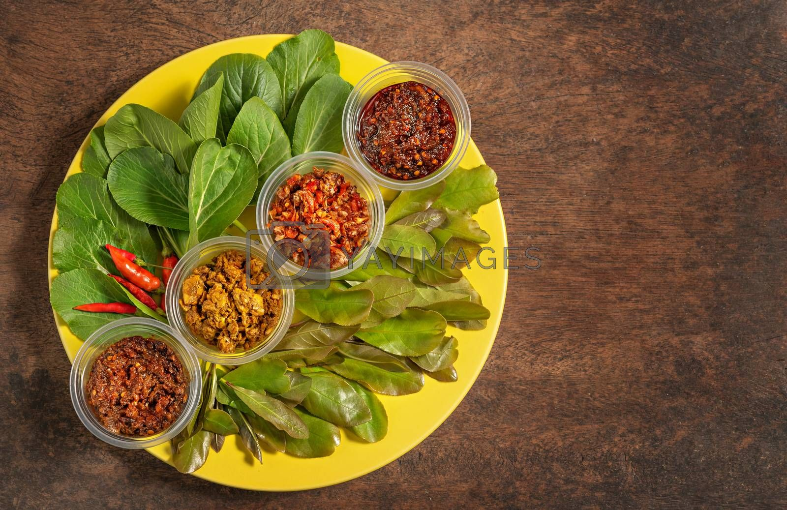 thai style chili paste served with fresh vegetables on yellow plate over wooden background