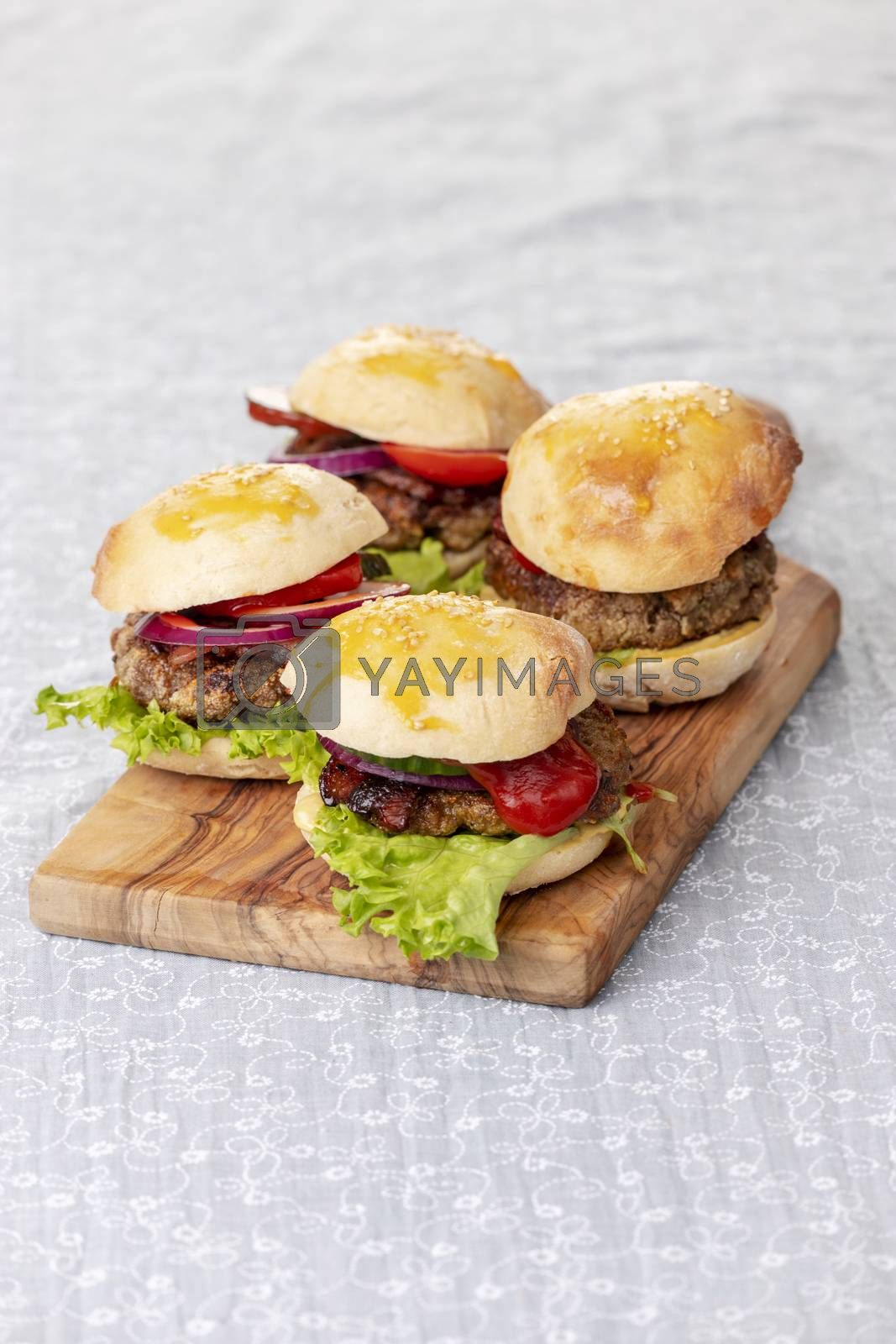 four small hamburges on a board by bernjuer
