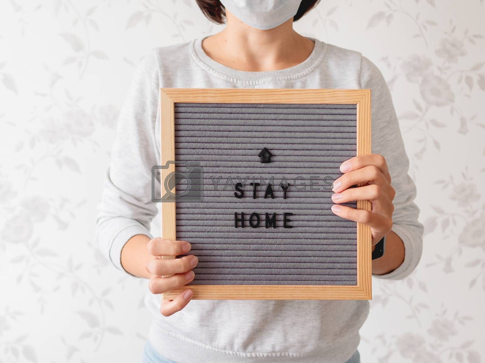 Woman in medical mask with letter board. Phrase STAY HOME. Quarantine because of coronavirus COVID19. Self-isolation at home.