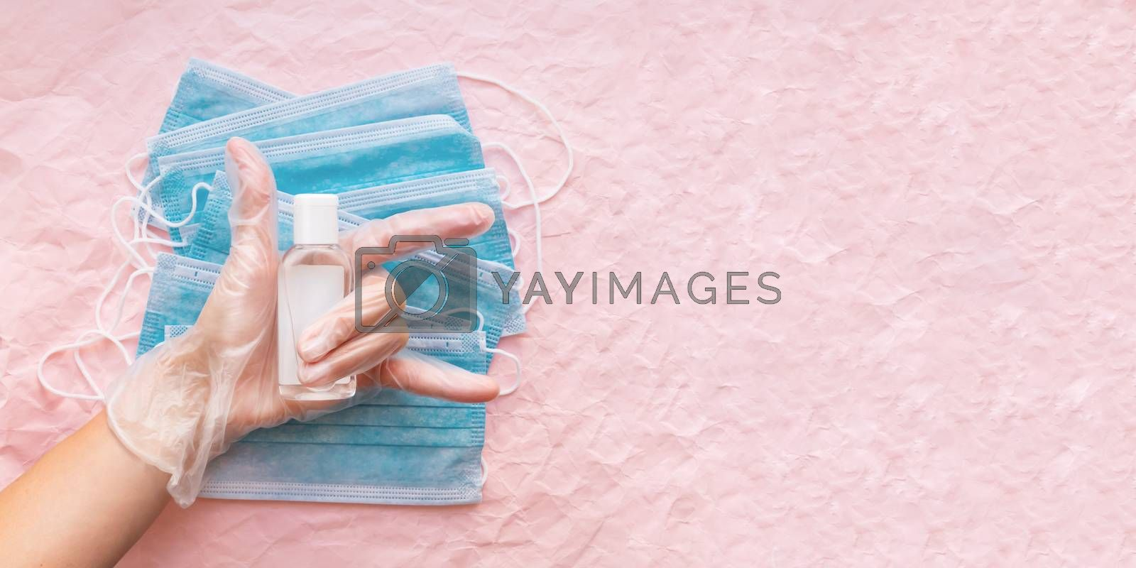 Top view on hand in protective gloves with medical masks and sanitizer in transparent bottle. Woman make victory gesture. Coronavirus COVID-19 concept on pink crumpled background with copy space.