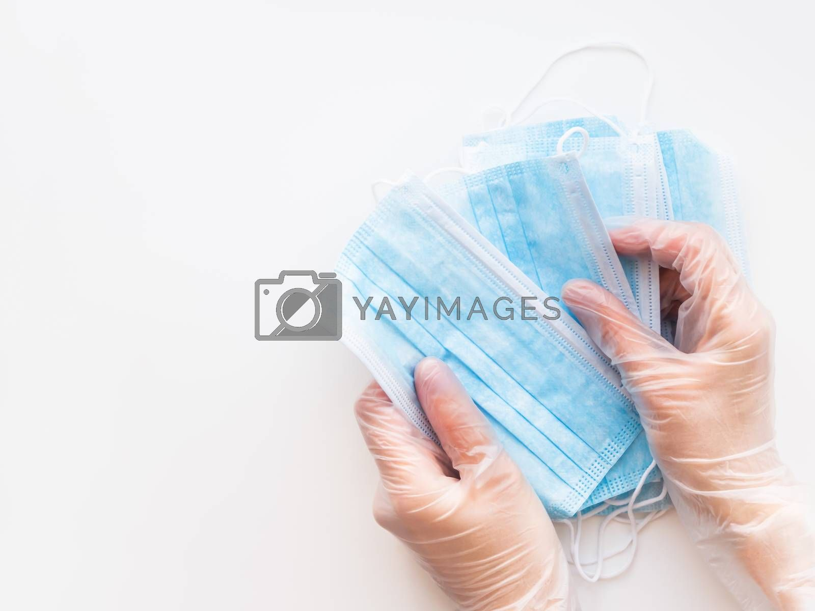 Top view on doctor's hands with pack of blue protective medical masks. Coronavirus COVID-19 concept on white background with copy space.