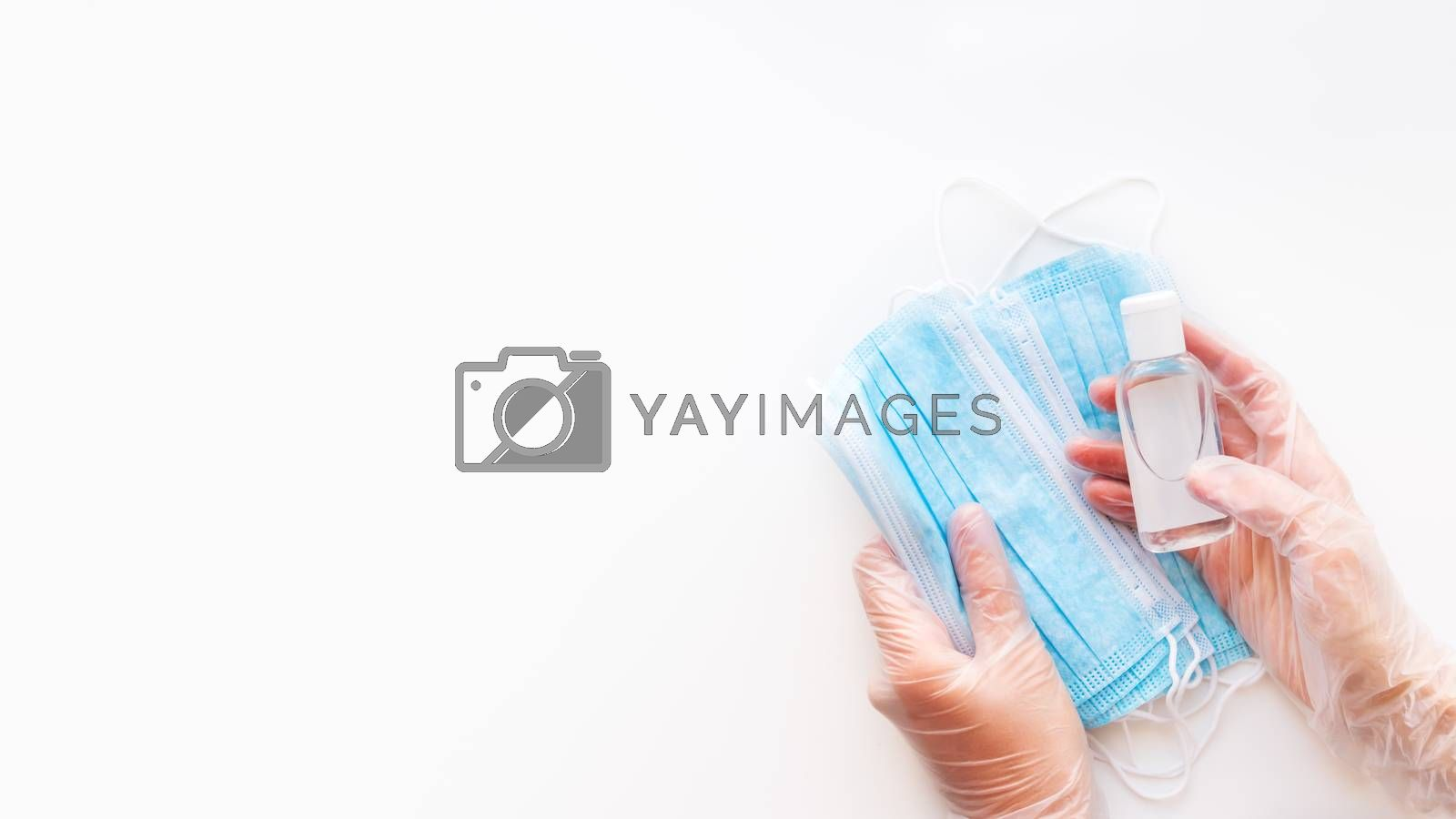 Top view on doctor's hands in protective gloves with medical masks and sanitizer in transparent bottle. Coronavirus COVID-19 concept on white background with copy space.