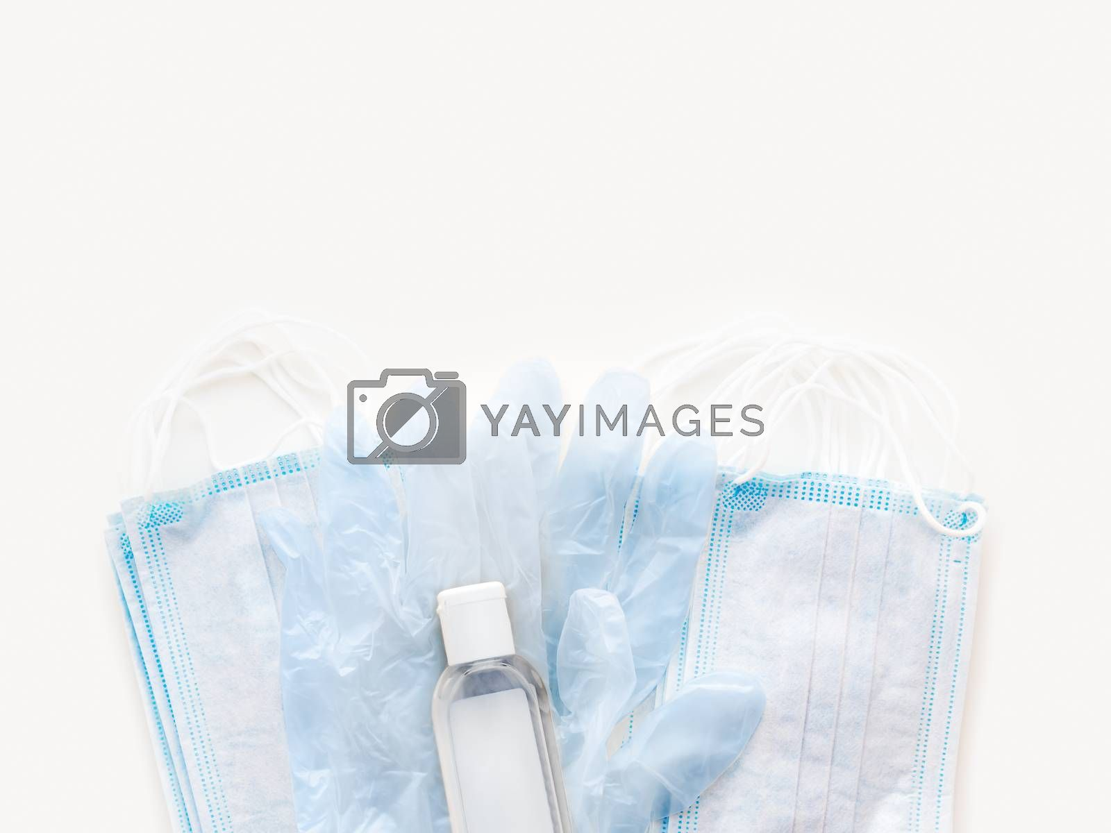 Top view on pack of blue medical masks, protective rubber gloves and transparent bottle with sanitizer gel. Coronavirus COVID-19 concept on white background.
