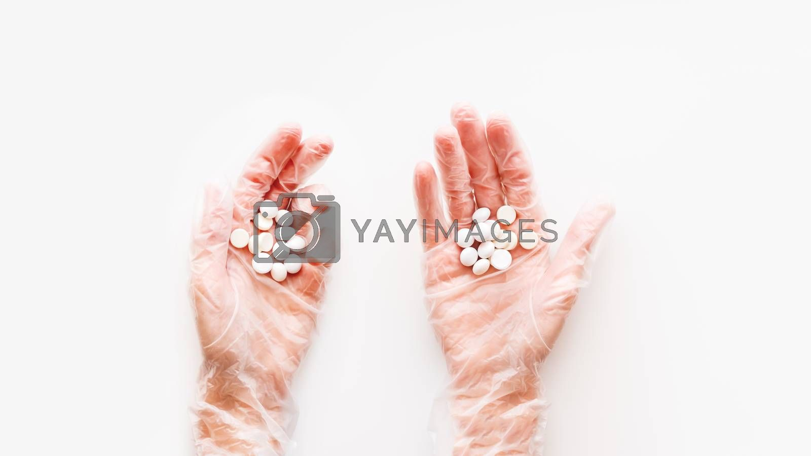 Doctor's palm hands in protective transparent gloves full of white scattering pills. Capsules with medicines on white background with copy space. Flat lay, top view.