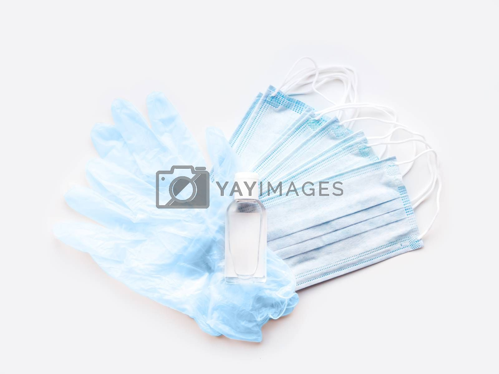 Top view on pack of blue medical masks, protective rubber gloves and transparent bottle with sanitizer gel. Heart shape. Coronavirus COVID-19 concept on white background.