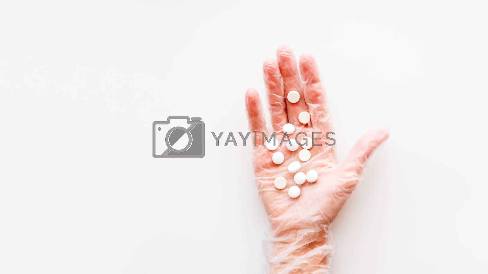 Doctor's palm hand in protective transparent glove full of white scattering pills. Capsules with medicines on white background with copy space. Flat lay, top view.