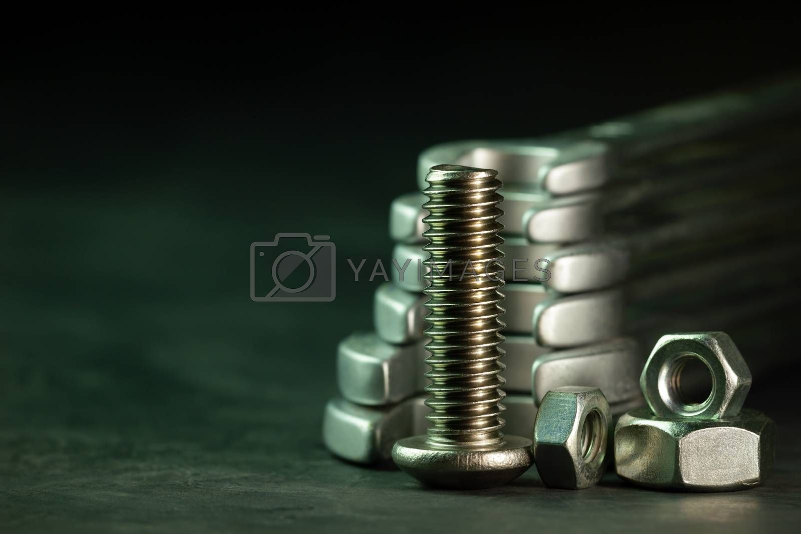 Bolt nuts and wrench on cement floor in darkness. Closeup and copy space for text. Concept of mechanical engineering jobs.