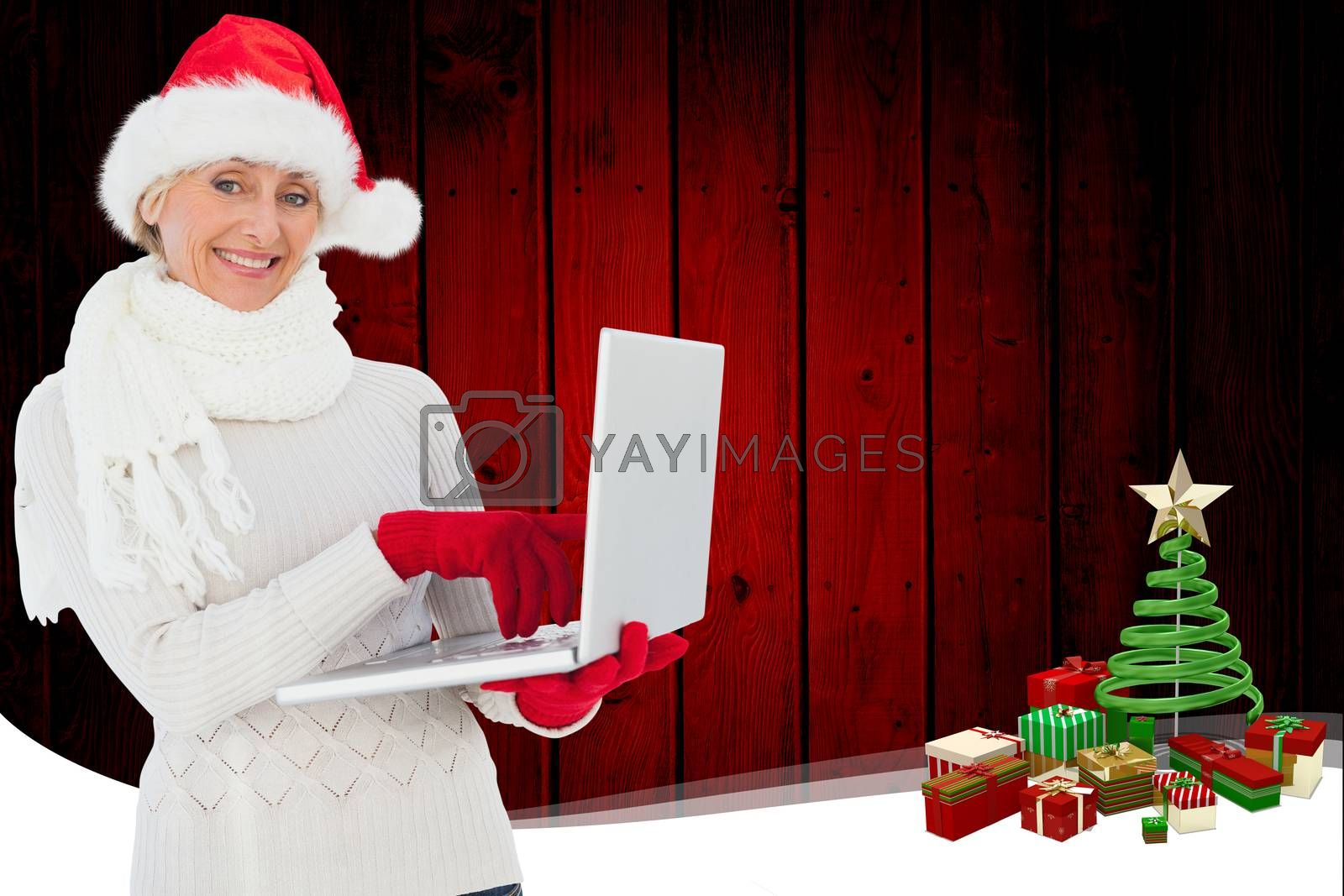 Festive woman holding laptop against christmas themed frame with tree
