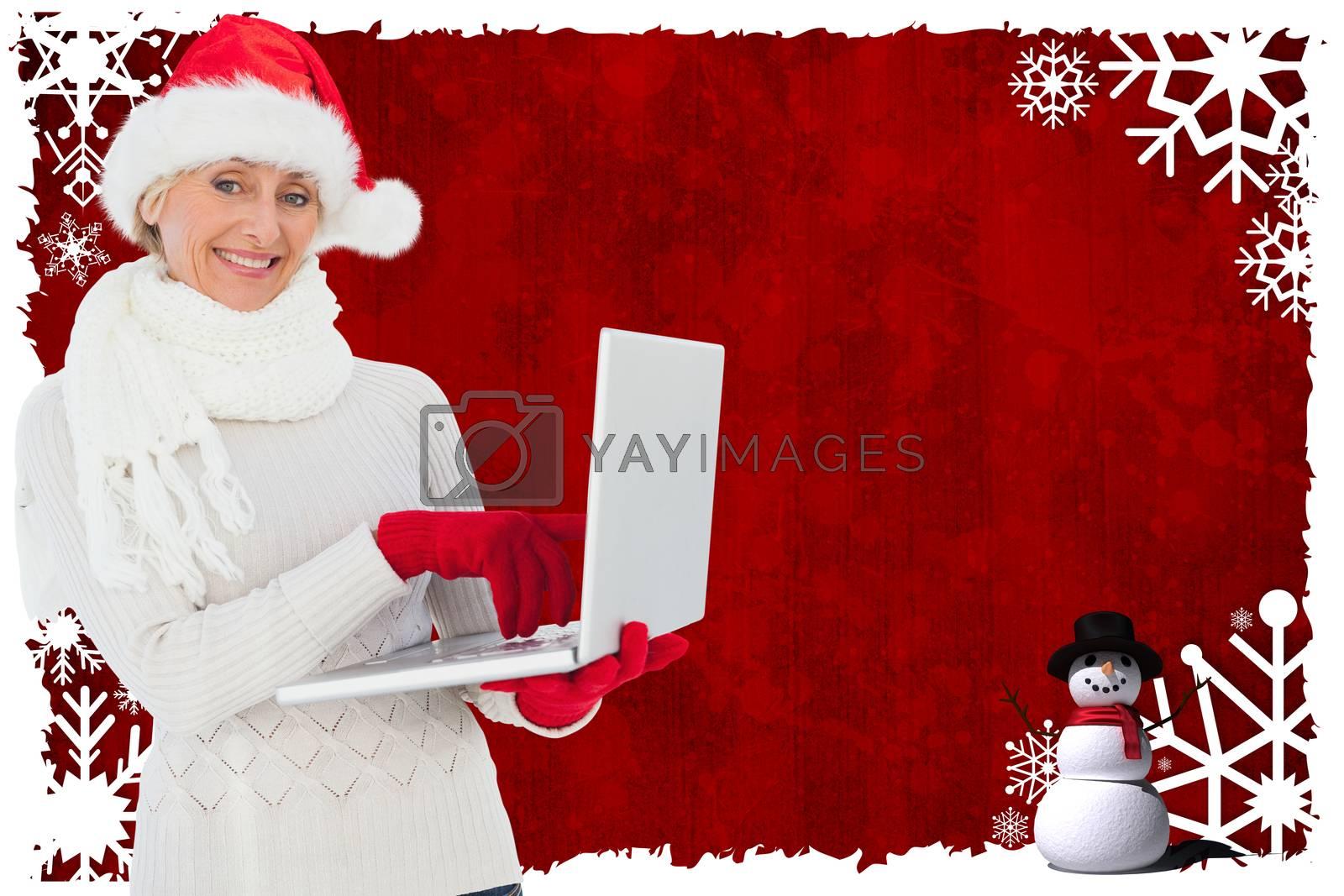 Festive woman holding laptop against christmas themed snow flake frame